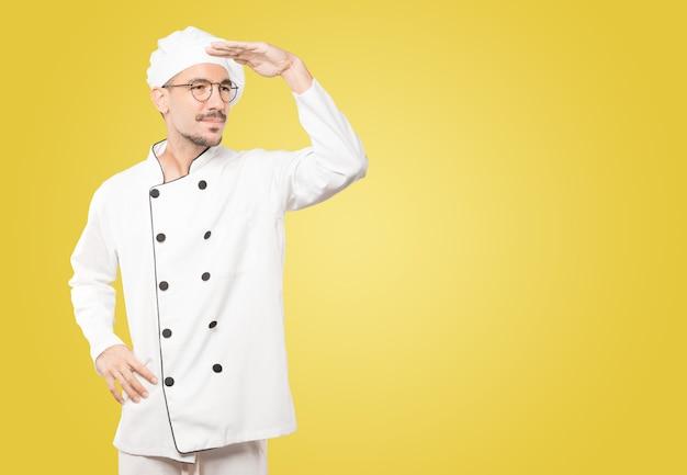 Giovane chef concentrato con un gesto di distogliere lo sguardo
