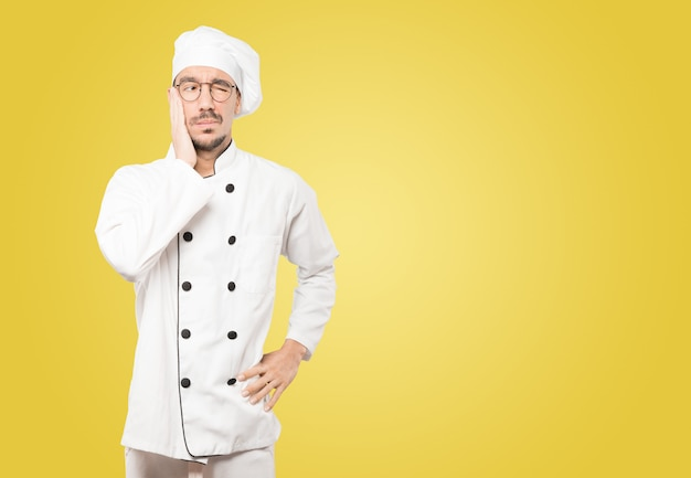 Giovane chef preoccupato che fa un gesto di preoccupazione