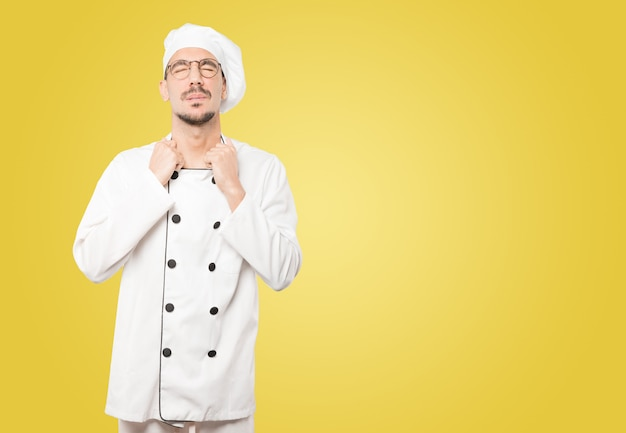 Giovane chef sollecitato che fa un gesto di ansia