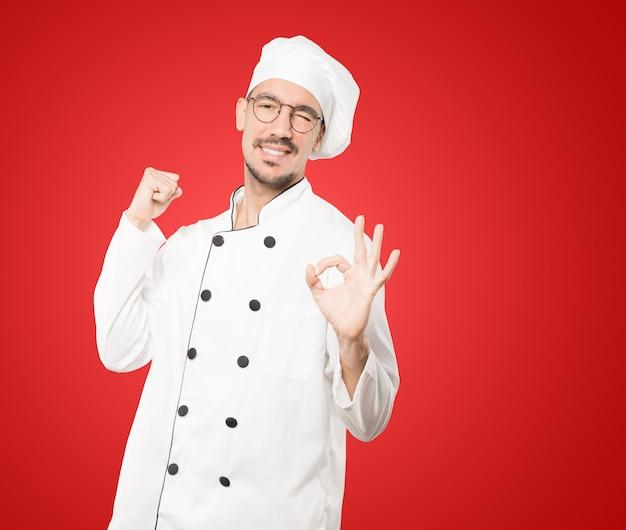 Giovane chef sorpreso con un gesto di approvazione