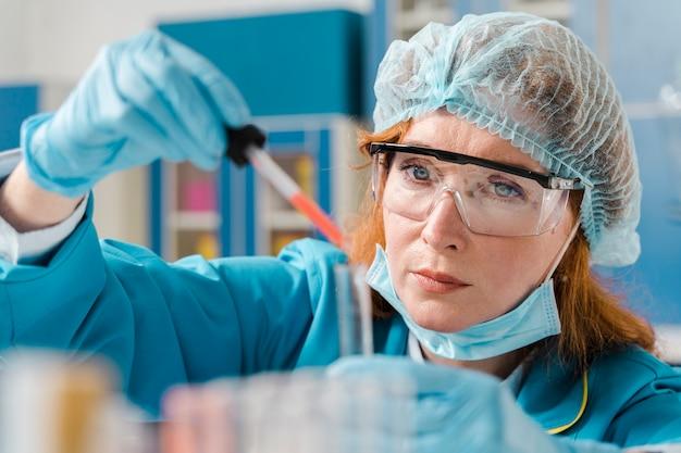 Giovane chimico della donna dello zenzero che esamina un campione