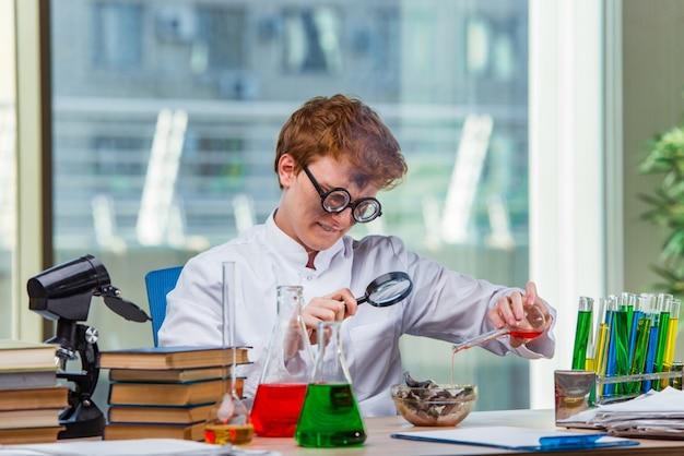 Giovane chimico pazzo che lavora in laboratorio