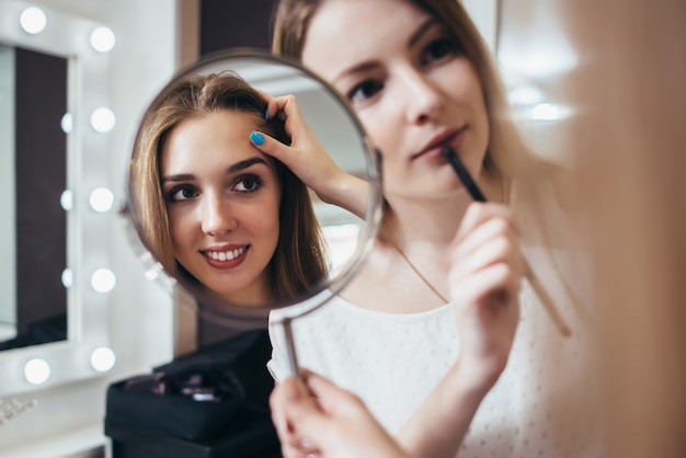 Giovane cliente femminile che si guarda allo specchio mentre truccatore che lavora alle sue sopracciglia nel salone di bellezza