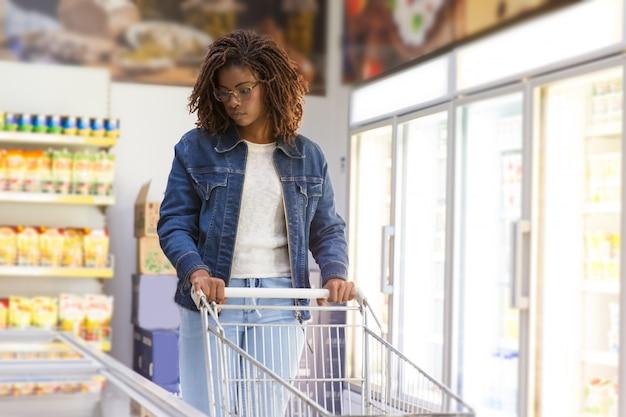Giovane cliente serio che sceglie le merci in congelatore