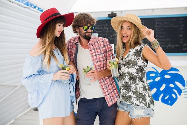 Giovane compagnia hipster di amici in vacanza al caffè estivo, bevendo cocktail mojito, felice stile positivo, sorridendo felice, due donne e un uomo che si divertono insieme, parlando, flirtare, romanticismo, tre