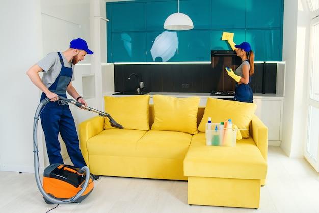 Giovane con aspirapolvere lavaggio con divano giallo vapore e bella donna pulisce i mobili della cucina.