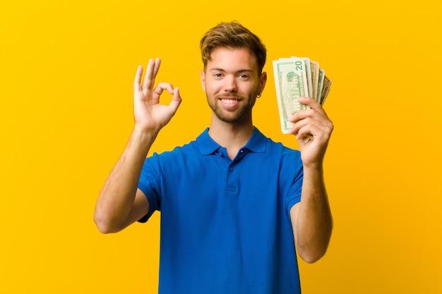Giovane con banconote su sfondo arancione