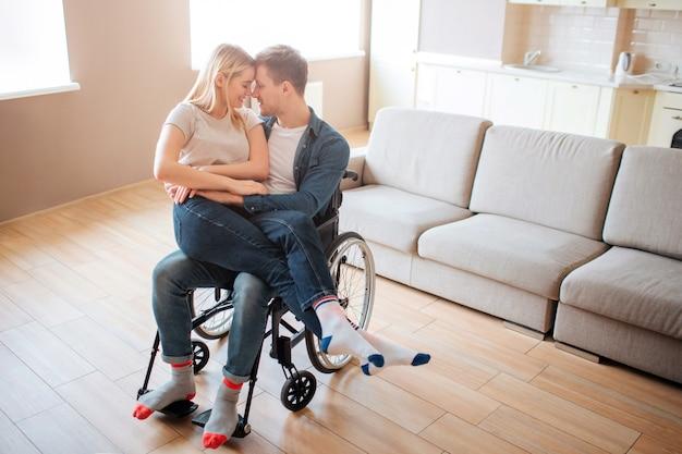 Giovane con disabilità e bisogni speciali che tengono fidanzata sulle ginocchia. si appoggiano l'un l'altro e sorridono. bella coppia felice insieme.