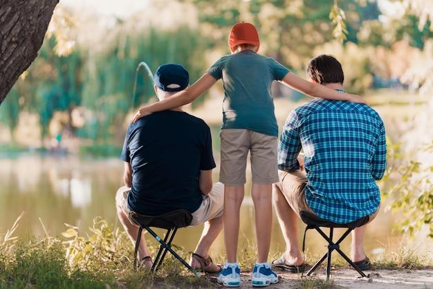 Giovane con figlio e padre pesca sul fiume.