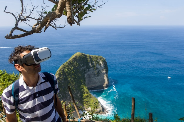Giovane con gli occhiali di vr alla spiaggia di kelingking sull'isola di nusa penida in indonesia