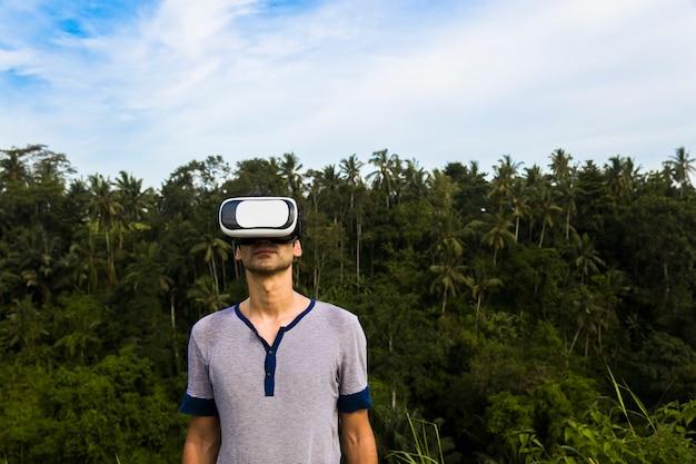 Giovane con gli occhiali vr nella foresta tropicale