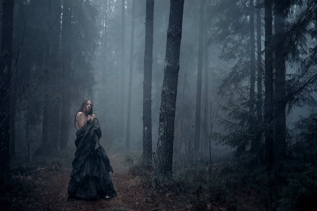 Giovane con i capelli lunghi nella foresta oscura