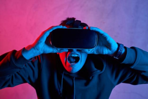 Giovane con il casco di realtà virtuale che grida alla macchina fotografica