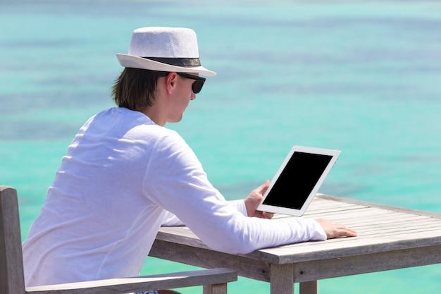 Giovane con il computer portatile alla spiaggia tropicale