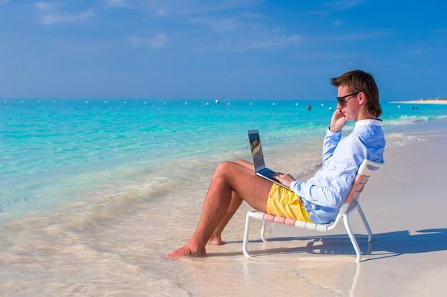 Giovane con il computer portatile e il telefono cellulare sulla spiaggia tropicale