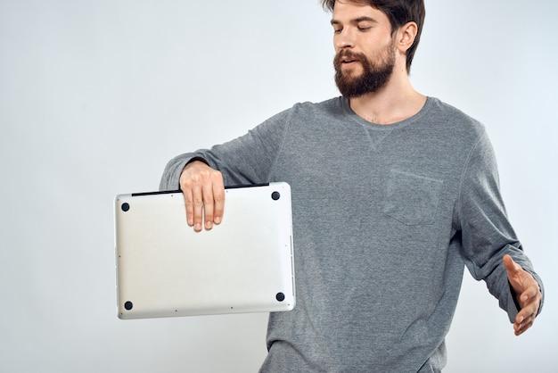 Giovane con il computer portatile in mano sulla a