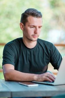 Giovane con il computer portatile nel caffè bevente del caffè all'aperto. uomo che usando smartphone mobile.