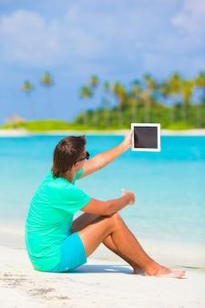 Giovane con il portatile in spiaggia tropicale