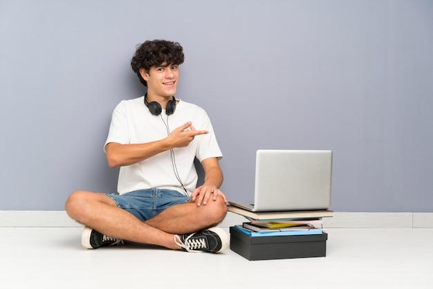 Giovane con il suo laptop seduto uno sul pavimento che estende le mani a lato per invitare a venire