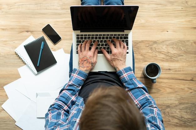 Giovane con il tatuaggio rosa a disposizione digitando sul computer portatile