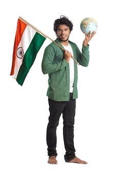 Giovane con la bandiera indiana o tricolore con il globo del mondo su superficie bianca, festa dell'indipendenza indiana, festa della repubblica indiana