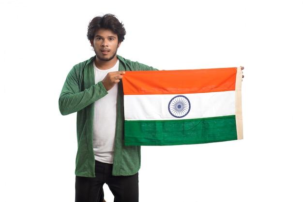 Giovane con la bandiera indiana o tricolore su fondo bianco, festa dell'indipendenza indiana, festa della repubblica indiana