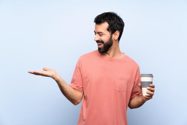 Giovane con la barba che tiene un caffè da asporto sopra il copyspace blu isolato della tenuta con due mani