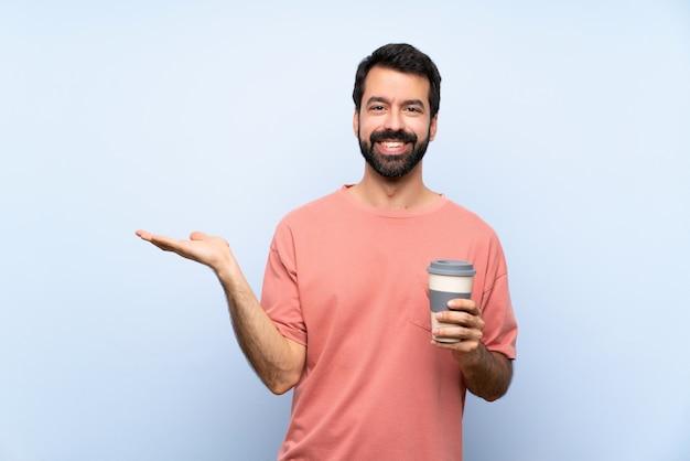 Giovane con la barba che tiene un caffè da asporto sopra il copyspace blu isolato della tenuta della parete immaginario sul palmo per inserire un annuncio