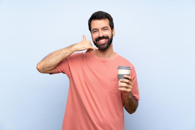 Giovane con la barba che tiene un caffè da asporto sopra il gesto di fabbricazione blu isolato del telefono
