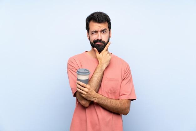 Giovane con la barba che tiene un caffè da asporto sopra il pensiero blu isolato della parete