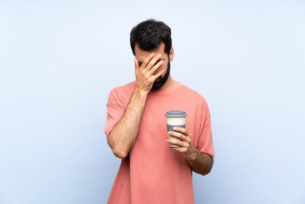 Giovane con la barba che tiene un caffè da asporto sopra l'azzurro isolato con l'espressione stanca e malata