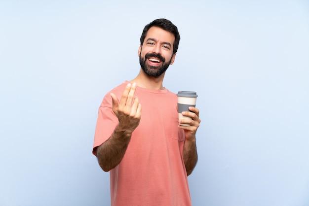 Giovane con la barba che tiene un caffè da asporto sopra la parete blu isolata che invita a venire con la mano