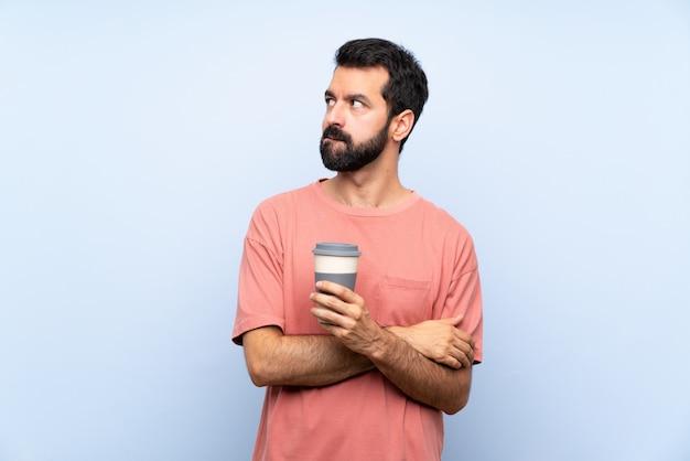 Giovane con la barba che tiene un caffè da asporto sopra la parete blu isolata con l'espressione confusa del fronte