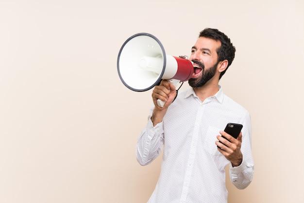 Giovane con la barba che tiene un cellulare che grida tramite un megafono