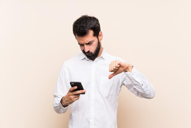 Giovane con la barba che tiene un cellulare che mostra pollice giù