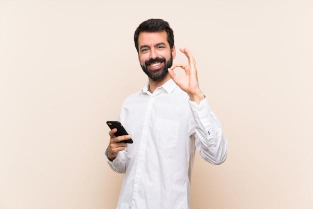Giovane con la barba che tiene un cellulare che mostra segno giusto con le dita