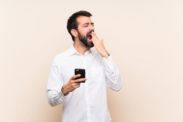 Giovane con la barba che tiene un cellulare che sbadiglia e che copre bocca spalancata con la mano