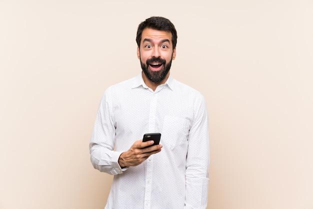 Giovane con la barba che tiene un cellulare con espressione facciale di sorpresa
