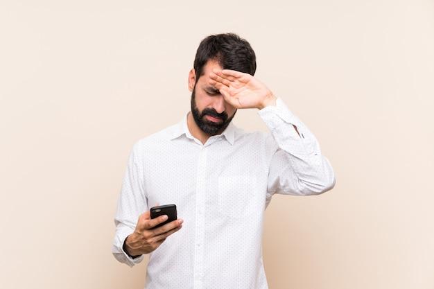 Giovane con la barba che tiene un cellulare con espressione stanca e malata