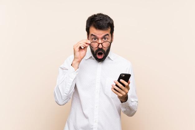 Giovane con la barba che tiene un cellulare con gli occhiali e sorpreso