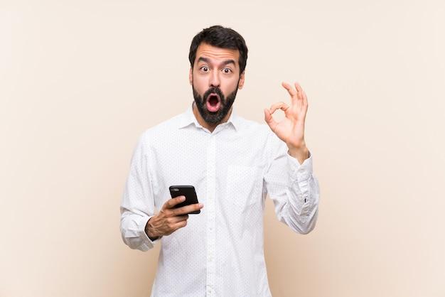 Giovane con la barba che tiene un cellulare sorpreso e che mostra segno giusto