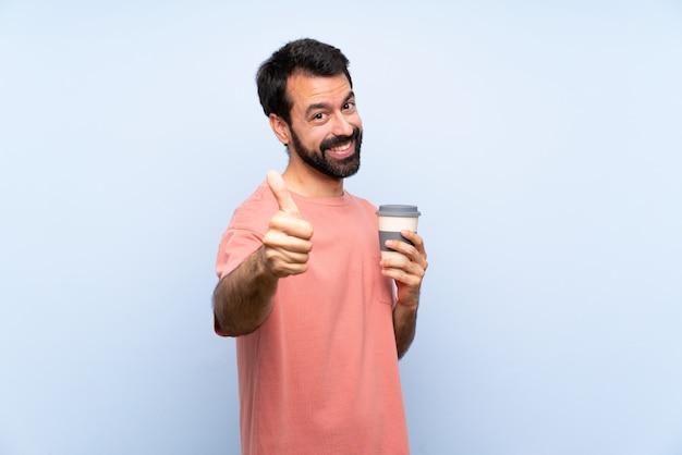Giovane con la barba in possesso di un caffè da asporto su blu isolato con il pollice in alto perché è successo qualcosa di buono