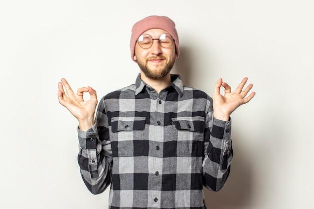 Giovane con la barba in un cappello, camicia a quadri e occhiali sta meditando o pregando su un bianco isolato. gesto di meditazione, relax