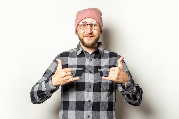 Giovane con la barba in un cappello, una camicia a scacchi fa un gesto di shaka su un bianco isolato. gesto di saluto