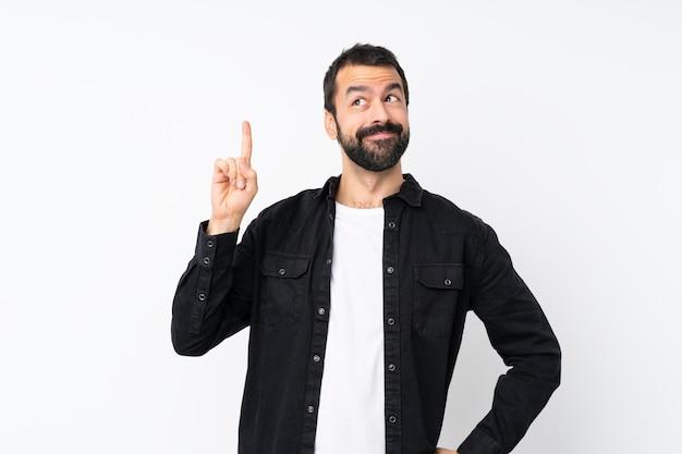 Giovane con la barba sopra bianco isolato che intende realizzare la soluzione mentre alza un dito