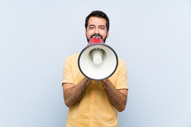 Giovane con la barba sopra il blu isolato che grida tramite un megafono