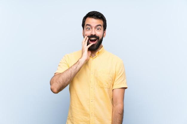 Giovane con la barba sopra il blu isolato con espressione facciale sorpresa e scioccata