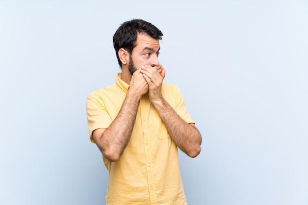 Giovane con la barba sopra la bocca blu isolata della copertura e guardare al lato