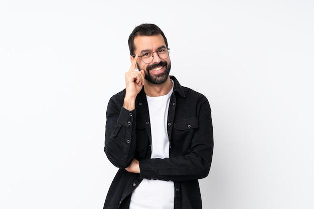 Giovane con la barba sopra la parete bianca isolata con gli occhiali e felice