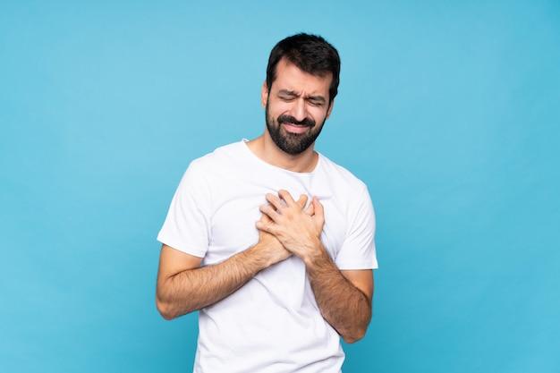 Giovane con la barba sopra la parete blu isolata che ha un dolore nel cuore